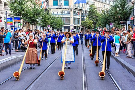 alphorn: Zurich, Switzerland - 1 August, 2016: participants of the parade devoted to the Swiss National Day passing along Bahnhofstrasse street. The Swiss National Day is the national holiday of Switzerland, set on 1 August. Editorial