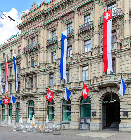 Zurich, Switzerland - 30 July, 2016: facade of the Credit Suisse building on Paradeplatz square, decorated with flags of Switzerland and Zurich. Credit Suisse Group is a Swiss multinational financial services holding company, headquartered in Zurich.