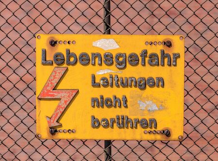stating: Basel, Switzerland - 27 August, 2016: a plate with the high voltage danger warning in German on the fence of a railroad area, stating the following Danger Do not touch the wires.