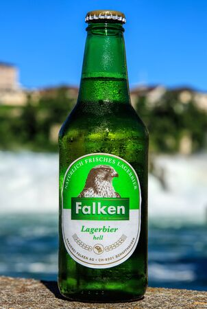 bier: Neuhausen am Rheinfall, Switzerland - 22 June, 2016: a bottle of Falken bier covered by drops of water, the Rhine Falls in the background. Falken (Falken is German for falcon) bier is produced by the Falken brewery in the Swiss city of Schaffhausen since  Editorial