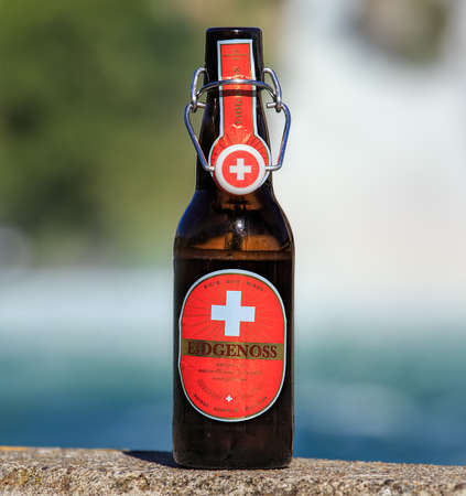 bier: Neuhausen am Rheinfall, Switzerland - 22 June, 2016: a bottle of Eidgenoss bier, the Rhine Falls in the background. Eidgenoss bier is brewed by the Falken brewery in the Swiss city of Schaffhausen. Editorial