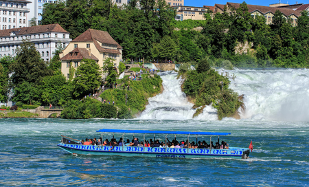 canto: Neuhausen am Rheinfall, Switzerland - 22 June, 2016: people in a boat on the the Rhine river, just below the Rhine Falls. The Rhine Falls is the largest plain waterfall in Europe, located on the Rhine river in Switzerland on the border between Swiss canto Editorial