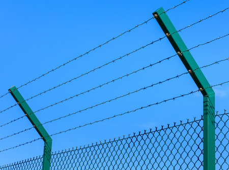 chainlink fence: Chain-link fence with barbed wires as its upper part against blue sky. Stock Photo
