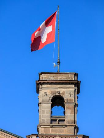 zurich: Flag of Switzerland on the Zurich main train station building in the city of Zurich, Switzerland. Zurich main train station building (German: Zurich HB) was opened in 1871. Stock Photo