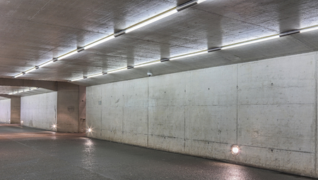 An underground passage with concrete walls and ceiling lit by fluorescent lamps.