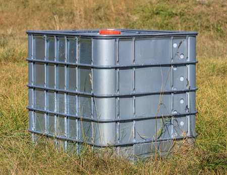 rounded edges: An abandoned 1000 liter canister for chemicals standing in grass. Stock Photo