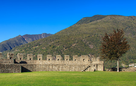 Wall of the medieval fortress Castelgrande in Bellinzona, Switzerland, mountains in the background. The Castelgrande fortress is a UNESCO World Heritage Site and also belongs to the Swiss Inventory of Cultural Property of National and Regional Significanc