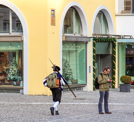 Zurich, Switzerland - 11 December, 2015: scene on the Munsterhof square in the old town of the city: a person in medieval clothing carrying a halberd, a person with a mobile phone, windows of a store with Christmas decorations. Zurich is the largest city