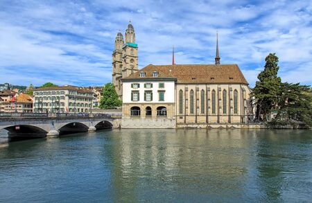 View in the city of Zurich, Switzerland: the Munsterbrucke bridge over the Limmat river, the Water Church, towers of the Grossmunster cathedral in the background.