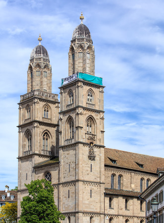 Zurich, Switzerland - 25 May, 2016: towers of the Grossmunster cathedral with a banner, which is a part of the promotion devoted to the World Refugee Day on the 20th of June, arranged by aid organization of Evangelic Churches of Switzerland (German: Hilfs