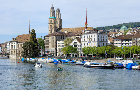 Zurich, Switzerland - 25 May, 2016: the Limmat river, historic buildings and towers of the Grossmunster Cathedral in the background. Zurich is the largest city in Switzerland and the capital of the Swiss canton of Zurich.