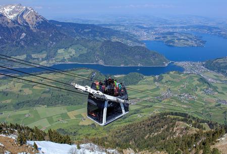 Mt. Stanserhorn, Svizzera - 7 maggio 2016: persone in una gondola della funivia Stanserhorn Cabrio, vertice del Monte. Pilatus e il Lago dei Quattro Cantoni sullo sfondo. Stanserhorn Cabrio è la prima funivia a doppio ponte aperta al mondo, trasporta 60 passeggeri