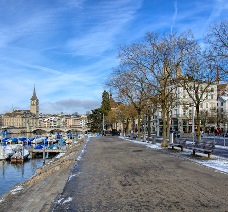 Zurich, Switzerland - 18 January, 2016: view along the Limmat river, St. Peter Church, Water Church and towers of the Grossmunster Cathedral in the background. Zurich is the largest city in Switzerland and the capital of the Swiss Canton of Zurich. Editorial