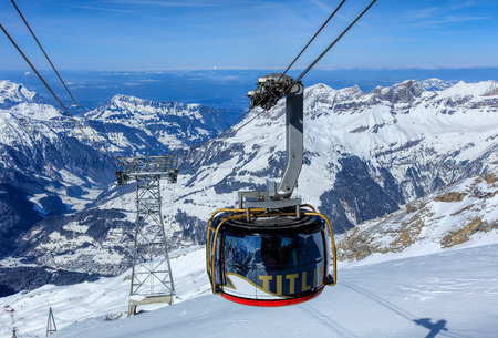 Mt. Titlis, Switzerland - 9 March, 2016: Rotair cable car gondola, view from the station on the top of the mountain. Rotair gondolas make a 360 degrees turn during the five-minute trip. Titlis is a mountain, located on the border between the Swiss Cantons