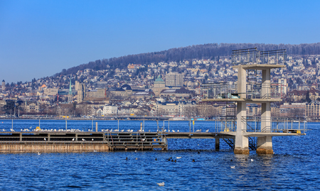 Zurich, Switzerland - 21 January, 2016: gulls on a platform on Lake Zurich on a somewhat foggy winter day, the city of Zurich in the background. Lake Zurich is a lake in Switzerland, extending southeast of the city of Zurich. Editorial