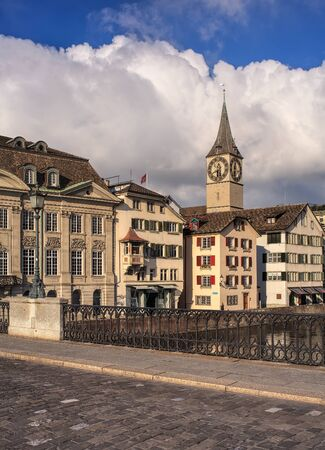 Zurich, Switzerland - 26 November, 2013: old town buildings along the Limmat river, clock tower of the St. Peter Church in the background - view from the Munsterbrucke bridge. Zurich is the largest city in Switzerland and the capital of the Swiss Canton o