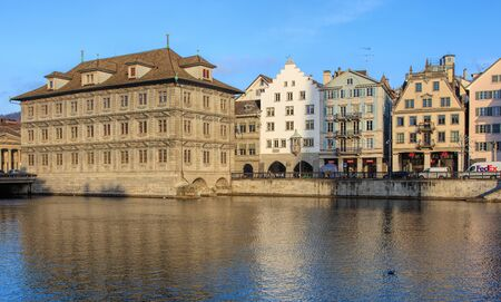 parliaments: Zurich, Switzerland - 19 December, 2016: the Limmat river and old town buildings along it. The leftmost building is the Zurich Town Hall (German: Rathaus), housing the city and canton parliaments.