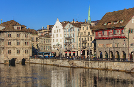 parliaments: Zurich, Switzerland - 27 December, 2016: historic buildings along the Limmat, people on the embankment of the river. The leftmost building is the Zurich City Hall (German: Rathaus), housing the city and cantonal parliaments. Zurich is the largest city in