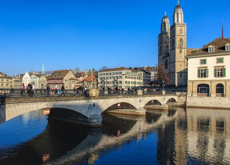 pedestrian bridges: Zurich, Switzerland - 1 January, 2017: people on the Munsterbrucke bridge. Munsterbrucke is a pedestrian and road bridge over the Limmat river in the city of Zurich, Switzerland. It is listed in the Swiss inventory of cultural property of national and reg