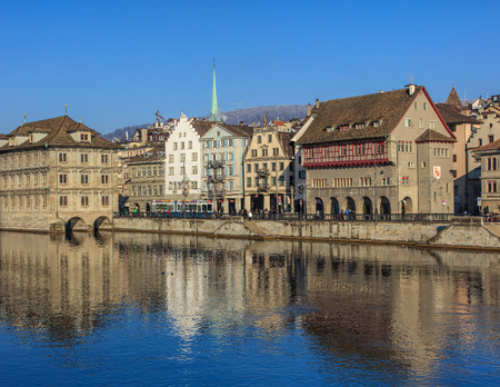 Zurich, Switzerland - 1 January, 2017: the Limmat river and historic buildings along it, people on the embankment. The leftmost building is the Zurich Town Hall (German: Rathaus), housing citys and cantons parliaments. Zurich is the largest city in Swit Editorial