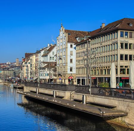 christmastime: Zurich, Switzerland - 1 January, 2017: the Limmat river, historic buildings, people on the embankment, Christmas illumination lamps temporarily installed along it for the Christmastime. Zurich is the largest city in Switzerland and the capital of the Swis