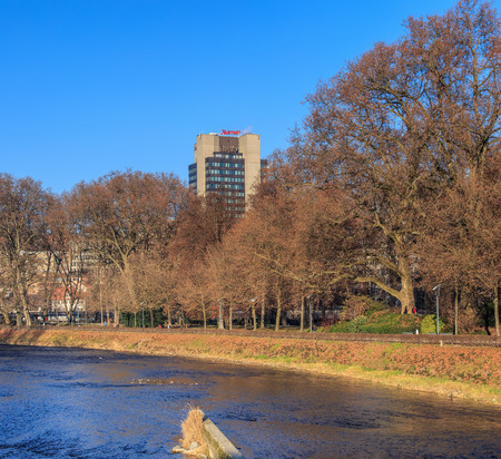 eventually: Zurich, Switzerland - 1 January, 2017: the Sihl river and the park along it, Hotel Marriott building in the background. The Sihl is a river that rises near the Druesberg mountain in the Swiss canton of Schwyz and eventually flows into the Limmat river in