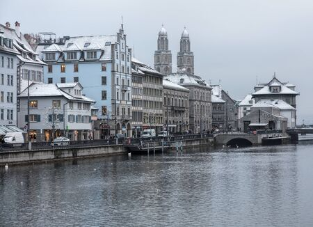Zurich, Switzerland - 3 January, 2017: historic buildings along the Limmat river, cars and people on the embankment of the river, Christmas illumination lamps temporarily installed along it for the Christmastime. Zurich is the largest city in Switzerland