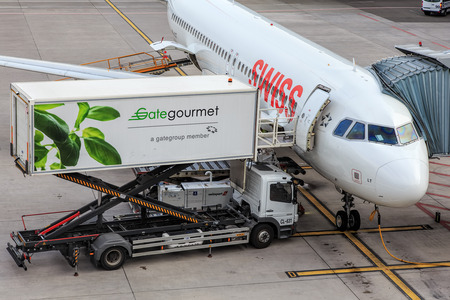 ag: Kloten, Switzerland - 5 August, 2015: a passenger airplane of the Swiss International Air Lines and a Gate Gourmets truck at a terminal in the Zurich Airport. Swiss International Air Lines AG (short Swiss) is the flag carrier airline of Switzerland. Gate Editorial