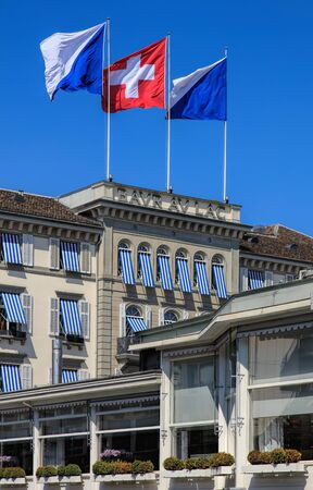 johannes: Zurich, Switzerland - 20 April, 2016: upper part of the Baur au Lac Hotel building decorated with flags of Zurich and Switzerland, view from Am Schanzengraben embankment. The Baur au Lac Hotel is a luxury hotel in Zurich, founded in 1844 by Johannes Baur. Editorial
