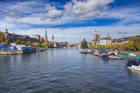 Zurich, Switzerland - 13 October, 2013: view along the Limmat river, towers of the Fraumunster, St. Peter Church and Grossmunster in the background. Zurich is the largest city in Switzerland and the capital of the Swiss Canton of Zurich.