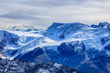 View from Mt. Titlis in the Swiss Alps on an overcast day in wintertime. Mount Titlis is a mountain, located on the border between the Swiss Cantons of Obwalden and Bern. Stock Photo