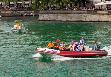 Zurich, Switzerland - 2 August, 2014: a police motorboat with paramedics on board on the Limmat river during the Street Parade. The Street Parade is the most attended technoparade in Europe, it takes place in the city of Zurich.