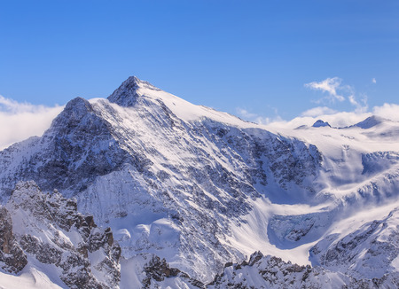 Alps, view from Mt. Titlis in Switzerland in winter. Titlis is a mountain, located on the border between the Swiss cantons of Obwalden and Bern. Stock Photo
