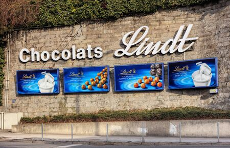 lindt: Zurich, Switzerland - 27 January, 2017: advertisement of Chocolats Lindt on a stone wall at Central square. Lindt is a brand of Lindt & Sprungli AG, more commonly known as Lindt - a Swiss confectionery company, founded in 1845.