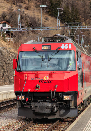 Filisur, Switzerland - 3 March, 2017: the locomotive of a Glacier Express train arriving to the Filisur railway station, selective focus on the front of the locomotive. The Glacier Express is a train, operated jointly by the Matterhorn Gotthard Bahn (MGB) Editorial