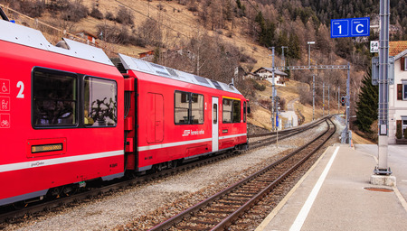 st german: Filisur, Switzerland - 3 March, 2017: a train of the Rhaetian Railway heading to the town of St. Moritz leaving the Filisur railway station. The Rhaetian Railway (Italian: Ferrovia Retica, German: Rhatische Bahn, abbreviated as RhB), is a Swiss transport