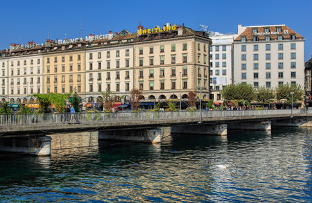 Geneva, Switzerland - 24 September, 2016: people on the Pont des Bergues bridge over the Rhone river, buildings along the river. The city of Geneva is the capital of the Swiss Canton of Geneva, it is the second most populous city in Switzerland.