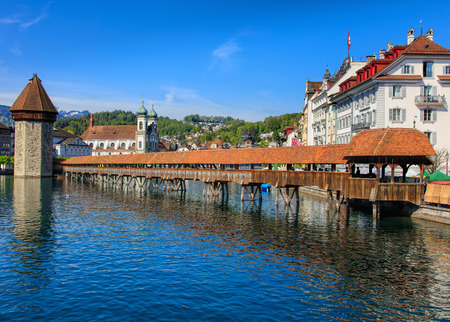 Lucerne, Switzerland - 7 May, 2016: the Chapel Bridge and the Water Tower. The Chapel Bridge (German: Kapellbrucke) is a covered wooden footbridge spanning diagonally across the Reuss in the city of Lucerne in Switzerland, named after the nearby St. Peter