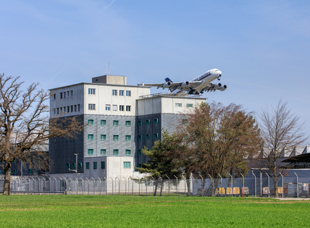 remand: Kloten, Switzerland - 29 March, 2017: Airbus A380 airplane of the Singapore Airlines flying above the Zurich Airport prison after taking off in the Zurich Airport. The Zurich Airport Prison (German: Flughafengefangnis) is an extradition and remand prison,