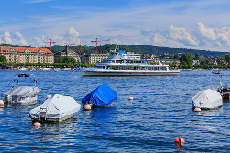 Zurich, Switzerland - 26 May, 2016: boats on Lake Zurich, MS Limmat approaching the city with passengers on board. Lake Zurich is a lake in Switzerland, extending southeast of the city of Zurich, which is the largest city in Switzerland and the capital of