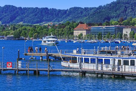 extending: Zurich, Switzerland - 18 June, 2017: boats and piers on Lake Zurich, people on the piers. Lake Zurich is a lake in Switzerland, extending southeast of the city of Zurich, which is the largest city in Switzerland.