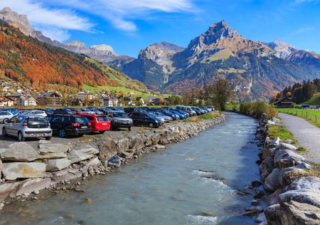 Engelberg, Switzerland - 12 October, 2015: cars on the parking lot at the Engelberger Aa river, mountains in the background. Engelberg is a resort town and municipality in the Swiss canton of Obwalden