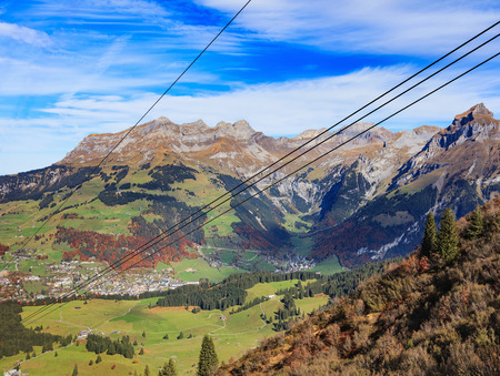 View from Mt. Titlis in Switzerland at the midle of autumn: summits of the Alps, town of Engelberg. The Titlis is a moutain located on the border between the Swiss cantons of Obwalden and Bern. Stock Photo