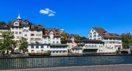 Zurich, Switzerland - 18 June, 2017: old town buildings along the Limmat river, people on the embankment of the river. Zurich is the largest city in Switzerland and the capital of the Swiss canton of Zurich.