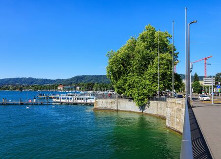 extending: Zurich, Switzerland - 18 June, 2017: embankment of Lake Zurich in the city of Zurich, people on piers, hills in the background, as seen from Quaibrucke bridge. Lake Zurich is a lake in Switzerland, extending southeast of the city of Zurich, which is the l Editorial