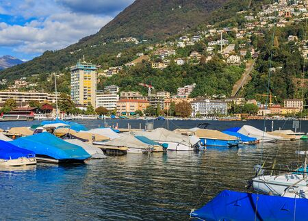 View in the city of Lugano in Switzerland: boats at a pier on Lake Lugano, buildings on the foot of the Monte Bre mountain in the background. Lugano is the largest city of the Swiss canton of Ticino. Stok Fotoğraf