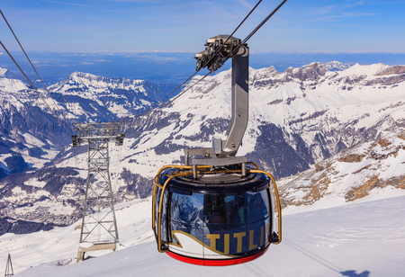 Mt. Titlis, Switzerland - 9 March, 2016: a gondola of the Rotair overhead cable car. Rotair gondolas make a 360 degrees turn during their trip. The Titlis is a mountain located on the border between the Swiss cantons of Obwalden and Bern, mainly accessed