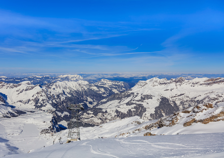 View from the Titlis mountain in Switzerland in wintertime. The Titlis is a mountain located on the border between the Swiss cantons of Obwalden and Bern, mainly accessed from the town of Engelberg on the northern side. Stock Photo