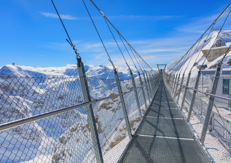 Suspension bridge on Mt. Titlis in wintertime. The Titlis is a mountain located on the border between the Swiss cantons of Obwalden and Bern, mainly accessed from the town of Engelberg on the northern side. Stock Photo