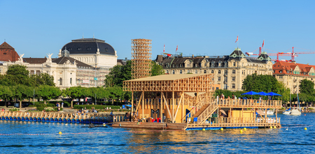 swimm: Zurich, Switzerland - 20 July, 2016: Pavilion of Reflections on Lake Zurich, people on the embankment of the lake, Zurich Opera House building in the background. The Pavilion of Reflections was a temporary floating island with an open-air cinema and swimm